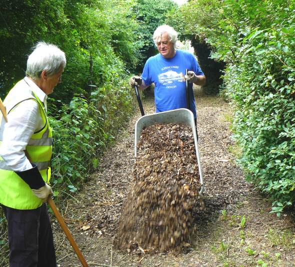 Gordon tipping wood chips onto the path